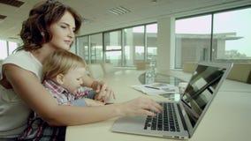 Bizneswoman pracuje na laptopie z dzieckiem zdjęcie wideo