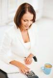 Bizneswoman pracuje z kalkulatorem w biurze Obraz Stock
