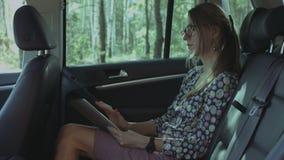 Bizneswoman pracuje z pastylka komputerem osobistym w luksusowym samochodzie zbiory wideo