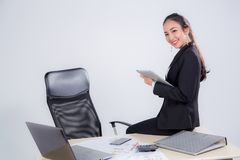 bizneswoman przyglądająca pastylka z obsiadanie stołem w biurze na białym tle Obrazy Stock