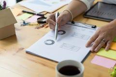 Bizneswoman ręki mienia pióro i analizować biznesowy zbiorczy ponownego Obrazy Royalty Free