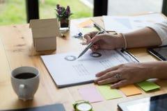Bizneswoman ręki mienia pióro i analizować biznesowy zbiorczy ponownego Fotografia Stock
