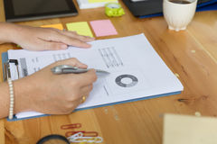 Bizneswoman ręki mienia pióro i analizować biznesowy zbiorczy ponownego Obraz Stock