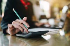 Bizneswoman ręki odciskanie na kalkulatorze dla kalkulować koszt e zdjęcia stock