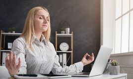 Bizneswoman relaksuje i medytuje przy miejscem pracy obraz royalty free
