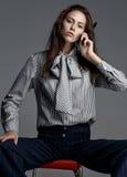 Bizneswoman rozmowa telefon komórkowy w studiu, siedzi na krześle Zdjęcie Royalty Free