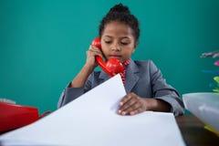 Bizneswoman sprawdza kartotekę podczas gdy opowiadający na ziemi linii Zdjęcia Stock