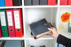Bizneswoman stawia dzienniczek w półce Fotografia Stock