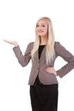 Bizneswoman stoi uśmiechniętego mienia jej ręka pokazuje somethin Zdjęcia Stock