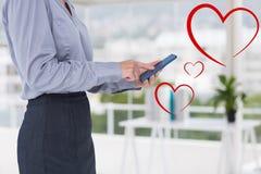 Bizneswoman texting obok cyfrowo wytwarzających czerwonych serc Obraz Stock