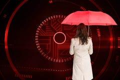 Bizneswoman trwanie kamery mienia czerwieni parasol z powrotem Zdjęcia Stock