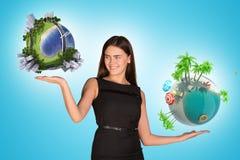 Bizneswoman trzyma dwa ziemskiej kuli ziemskiej Obraz Stock