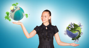 Bizneswoman trzyma dwa ziemskiej kuli ziemskiej Zdjęcie Stock