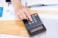 Bizneswoman trzyma pióro i analizuje marketingowego plan z kalkulatorem na drewnianym biurku w biurze pojęcia tła diety jaj złoty obraz royalty free