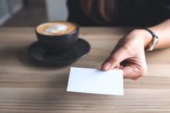 Bizneswoman trzyma pustą wizytówkę i daje someone z filiżanką na stole Zdjęcia Stock