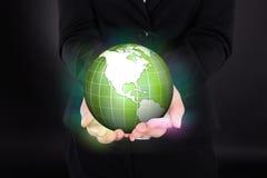 Bizneswoman trzyma rozjarzoną zieloną kulę ziemską Obrazy Royalty Free