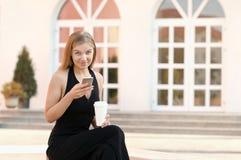 Bizneswoman używa telefon komórkowego i pijący kawę na przerwie przy plenerowym zdjęcie stock