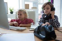Bizneswoman używa komputer w biurze podczas gdy męski kolega opowiada na telefonie Obrazy Royalty Free