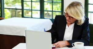 Bizneswoman używa laptop podczas gdy mieć kawę 4k zbiory wideo