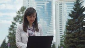 Bizneswoman U?ywa laptop w miasto parku zbiory wideo