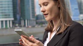 Bizneswoman używa mądrze telefon w miasta śródmieściu, fachowy żeński odbiorczy dobre wieści excited zbiory