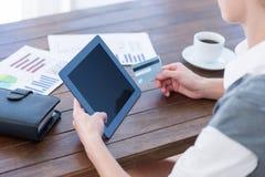 Bizneswoman używa pastylka komputer osobistego i trzymający kredytową kartę Zdjęcia Royalty Free