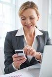 Bizneswoman Używa telefon komórkowego Wysyłać wiadomość tekstową W biurze zdjęcia stock