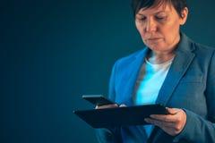 Bizneswoman używa telefonu komórkowego i pastylki komputer obraz royalty free