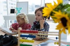 Bizneswoman używa komputer w biurze podczas gdy coworker opowiada na telefonie Fotografia Royalty Free