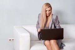 Bizneswoman używa laptopu obsiadanie na kanapie przy biurem zdjęcie stock