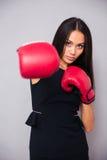 Bizneswoman uderza pięścią przy kamerą w bokserskich rękawiczkach obraz royalty free