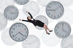 Bizneswoman unosi się wśród zegarów Obraz Stock