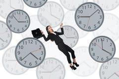 Bizneswoman unosi się wśród zegarów Obraz Royalty Free
