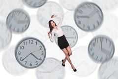 Bizneswoman unosi się wśród zegarów Fotografia Stock