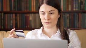 Bizneswoman w białym koszulowym obsiadaniu na kanapie w żywym izbowym kupieniu online z kredytową kartą na laptopie zbiory