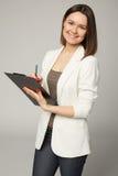 Bizneswoman w białej kurtce pisze na schowku Zdjęcia Stock