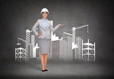 Bizneswoman w hełmie pokazuje budowę Fotografia Royalty Free