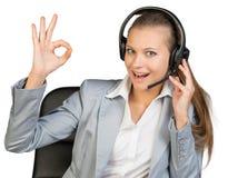 Bizneswoman w słuchawki robi zadowalającemu gestowi Zdjęcie Stock