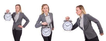 Bizneswoman w szarość nadaje się mienie budzika odizolowywającego na bielu Zdjęcie Stock