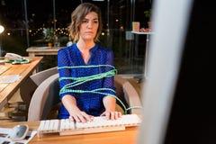 Bizneswoman wiązał z arkaną podczas gdy pracujący na komputerze przy jej biurkiem Zdjęcia Stock