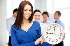 Bizneswoman wskazuje przy budzikiem Zdjęcia Royalty Free