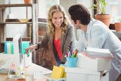 Bizneswoman wskazuje w kierunku komputeru w biurze Obraz Royalty Free