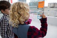 Bizneswoman wyjaśnia męski kolega podczas gdy pisać na okno w biurze Obrazy Stock