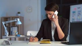 Bizneswoman wzywa smartphone przy ciemnym biurem zbiory wideo