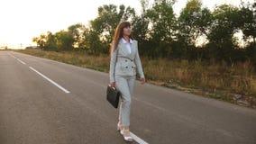 Bizneswoman z czarnymi teczka spacerami w lekkim kostiumu i bielu heeled buty iść na zewnątrz miasta wzdłuż asfaltu z zbiory wideo