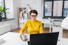 Bizneswoman z laptopem pije kaw? przy biurem zdjęcie royalty free