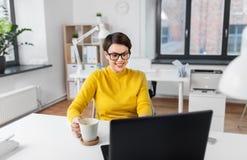 Bizneswoman z laptopem pije kaw? przy biurem obraz royalty free