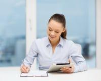 Bizneswoman z pastylka komputerem osobistym i kartoteki w biurze Obraz Stock