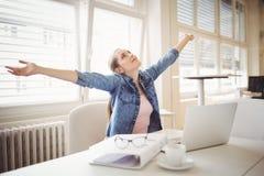 Bizneswoman z rękami szeroko rozpościerać podczas gdy siedzący przy biurem Obraz Stock