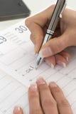 Bizneswoman zauważa spotkanie w jej dzienniczku w biurze, Zdjęcie Royalty Free